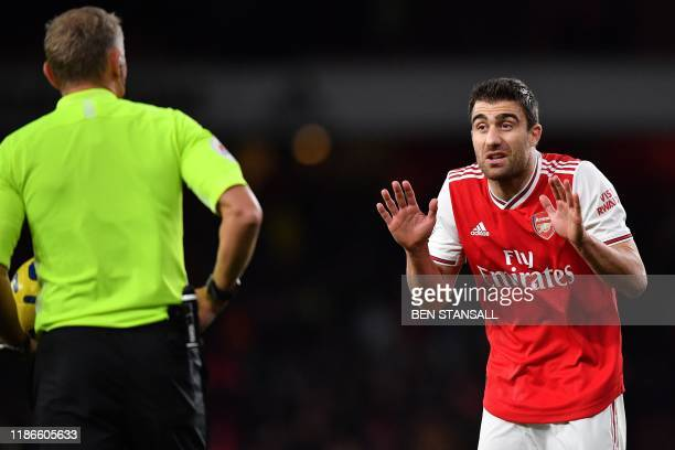 Arsenal's Greek defender Sokratis Papastathopoulos pleads with Referee Graham Scott after receiving a yellow card during the English Premier League...