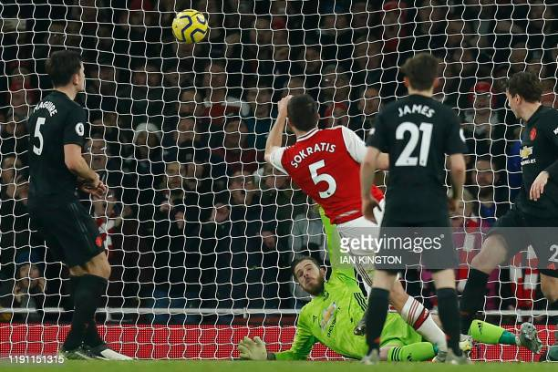 TOPSHOT Arsenal's Greek defender Sokratis Papastathopoulos shoots past Manchester United's Spanish goalkeeper David de Gea to score their second goal...