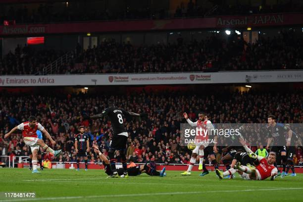 Arsenal's Greek defender Sokratis Papastathopoulos shoots to score what he thinks is their third goal but after a VAR review it is ruled out during...