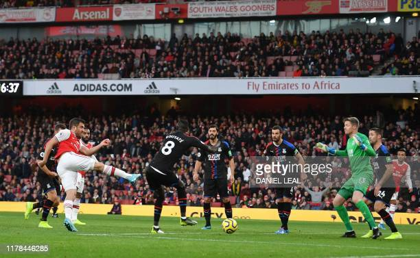 Arsenal's Greek defender Sokratis Papastathopoulos shoots to score the opening goal of the English Premier League football match between Arsenal and...