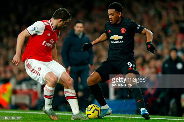 Arsenal's Greek defender Sokratis Papastathopoulos vies with Manchester United's French striker Anthony Martial during the English Premier League...