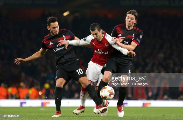 Arsenal's Henrikh Mkhitaryan and AC Milan's Hakan Calhanoglu and iccardo Montolivo battle for the ball during the UEFA Europa League round of 16...