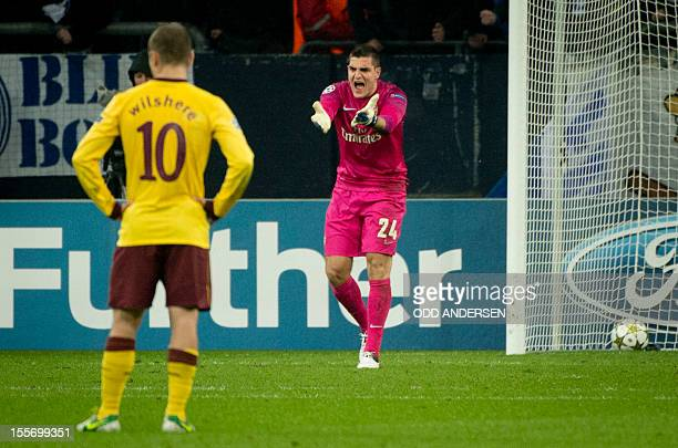 Arsenal´s Italian goalkeeper Vito Mannone and Arsenal´s midfielder Jack Wilshere reacts as the ball lies in the net after Schalke's Dutch striker...