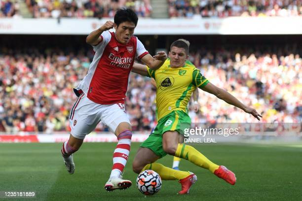 Arsenal's Japanese defender Takehiro Tomiyasu vies with Norwich City's Scottish midfielder Billy Gilmour during the English Premier League football...