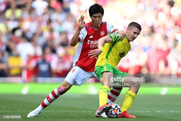 Arsenal's Japanese defender Takehiro Tomiyasu vies with Norwich City's Polish midfielder Przemys?aw P?acheta during the English Premier League...