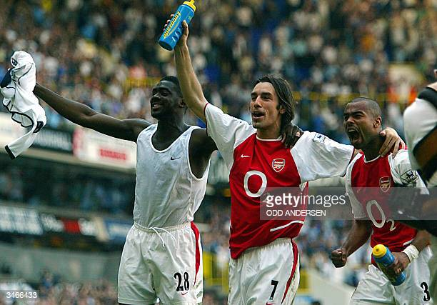 Arsenal's Kolo Toure Robert Pires and Ashley Cole celebrate winning the 2003/2004 Football Premier League after drawing 22 with Tottenham in their...