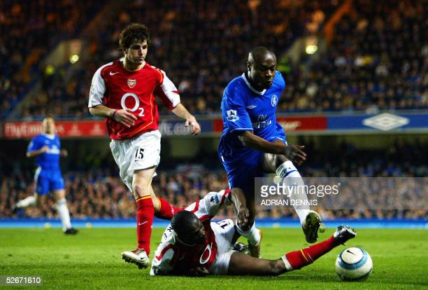 Arsenal's Lauren makes a tackle on William Gallas of Chelsea while Cesc Fabregas looks on during the Premiership match at Stamford Bridge in London...