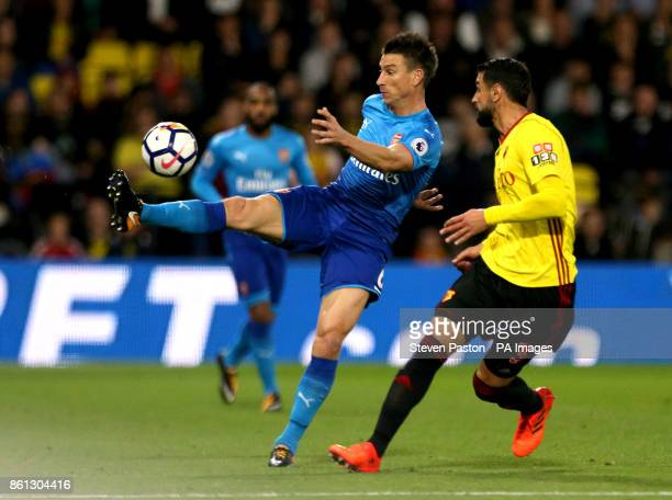 Arsenal's Laurent Koscielny and Watford's Miguel Britos battle for the ball during the Premier League match at Vicarage Road Watford