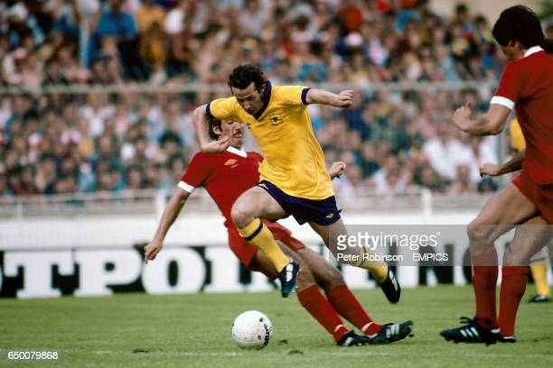 Arsenal's Liam Brady skips over a challenge from Liverpool's Alan Kennedy
