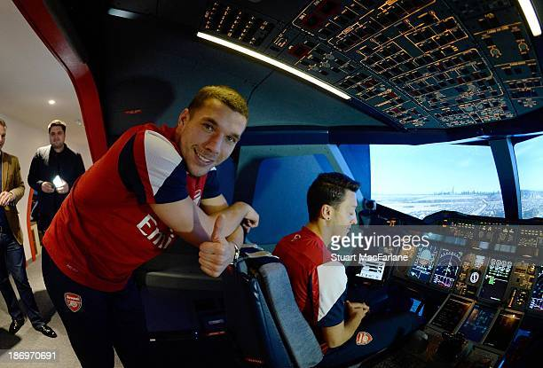 Arsenal's Lukas Podolski and Mesut Oezil in the Emirates' A380 flight simulator on October 31 2013 in Greenwich England