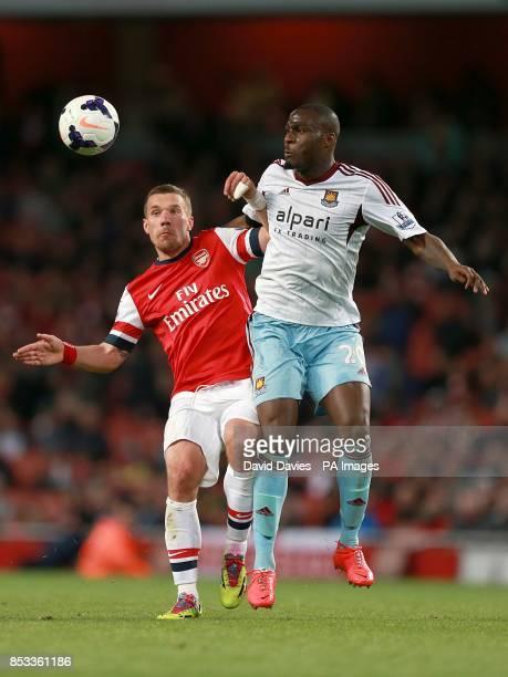 Arsenal's Lukas Podolski and West Ham United's Guy Demel battle for the ball