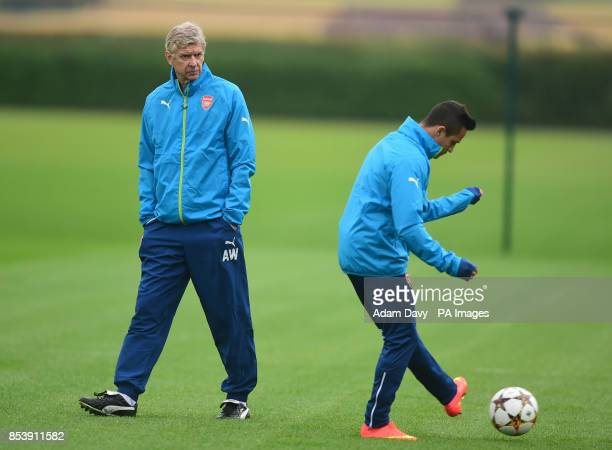 Arsenal's Manager Arsene Wenger watches Alexis Sanchez during a training session at London Colney Hertfordshire