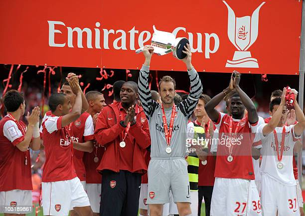 Arsenal's Manuel Alumnia lifts the Emirates trophy after beating Celtic's after their Emirates Cup football match at Emirates Stadium in London on...