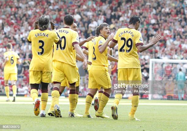 Arsenal's Marouane Chamakh celebrates with team mates after his shot hit the post and bounced of Liverpool goalkeeper Jose Reina for his sides first...
