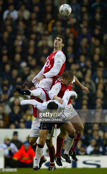 Arsenal's Martin Keown rises above his teammates Freddie Ljungberg and Ray Parlour as Gustavo Payet of Tottenham Hotspur gets pushed down during the...
