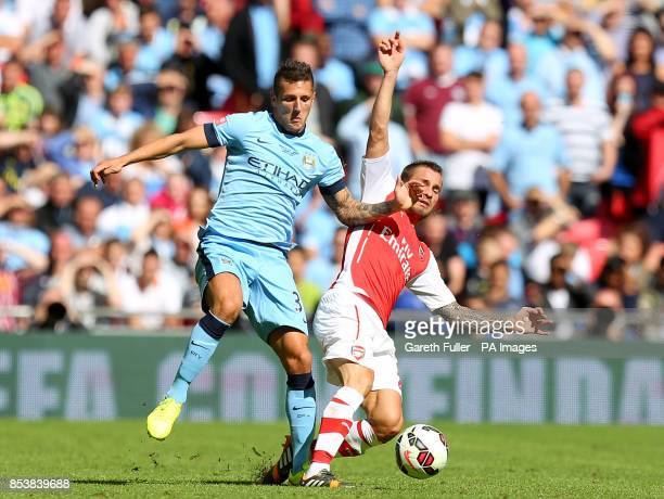 Arsenal's Mathieu Debuchy and Manchester City's Stevan Jovetic battle for the ball during the Community Shield match at Wembley Stadium London