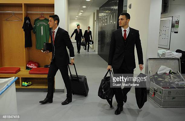 Arsenal's Mesut Oezil and Thomas Vermaelen arrive in the changing room before the match at Emirates Stadium on November 23 2013 in London England