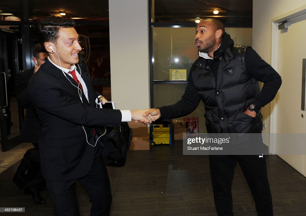 Arsenal's Mesut Oezil shakes hands with former player Thierry Henry before the UEFA Champions League match between Arsenal and Olympique de Marseille, at Emirates Stadium on November 26, 2013 in London, England.