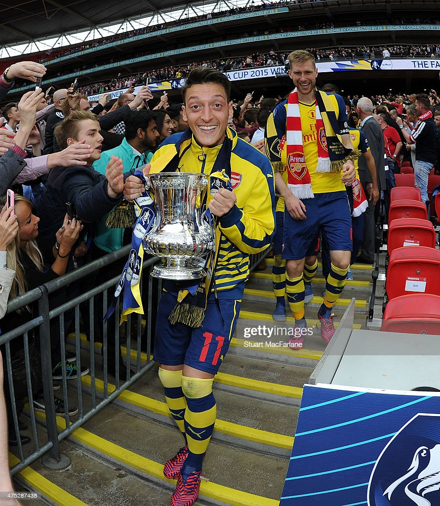 Arsenal's Mesut Oizil celebrates after the FA Cup Final between Aston Villa and Arsenal at Wembley Stadium on May 30, 2015 in London, England.