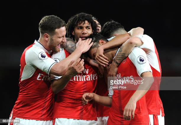 Arsenal's Mesut Ozil celebrates scoring a goal for Arsenal with Mohamed Elneny and Shkodran Mustafi during the Premier League match between Arsenal...