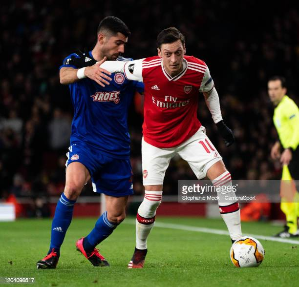 Arsenal's Mesut Ozil shields the ball from Olympiakos' Andreas Bouhalakis during the UEFA Europa League round of 32 second leg match between Arsenal...