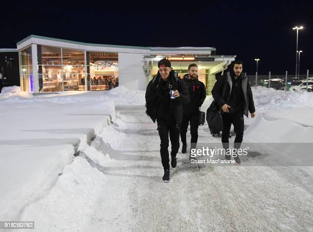 Arsenal's Mesut Ozil Shkodran Mustafi and Sead Kolasinac walk from the terminal to team bus at Ostersund airport on February 14 2018 in Ostersund...