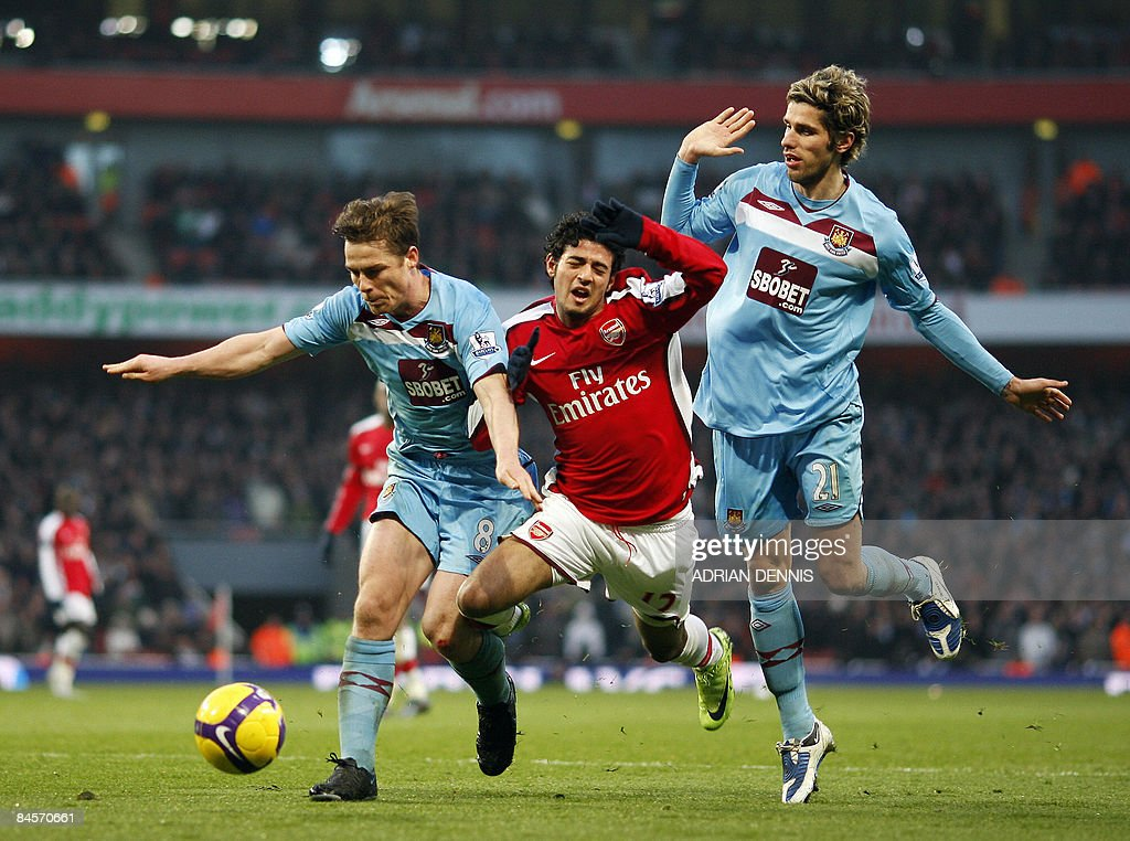 Arsenal's Mexican player Carlos Vela (C) loses his balance after a challenge from West Ham's Scott Parker (L) and Valon Behrami during their Premiership match at The Emirates Stadium in London on January 31, 2009. Vela was booked for diving in the penalty area. The game ended in a 0-0 tie. AFP PHOTO / Adrian Dennis --- FOR EDITORIAL USE ONLY Additional licence required for any commercial/promotional use or use on TV or internet (except identical online version of newspaper) of Premier League/Football League photos. Tel DataCo +44 207 2981656. Do not alter/modify photo.