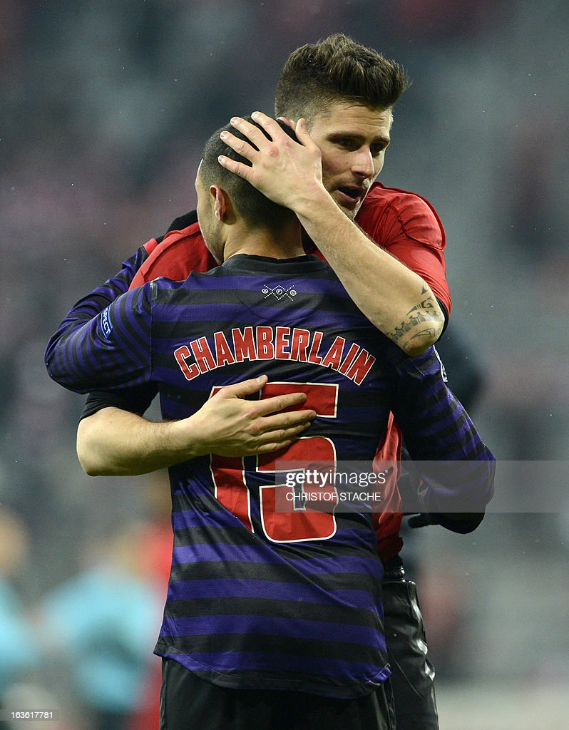 Arsenal's midfielder Alex Oxlade-Chamberlain embraces Arsenal's French striker Olivier Giroud (R) after the the UEFA Champions League round of 16 second leg football match between FC Arsenal London and FC Bayern Munich in the stadium in in Munich, southern Germany, on March 13, 2013. Bayern lost 0:2 but qualified for the quarter-finals.