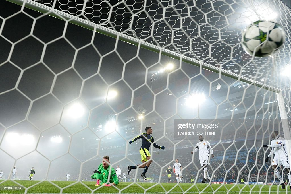 TOPSHOT - Arsenal's Nigerian forward Alex Iwobi (C) scores a goal despite of Basel's Czech goalkeeper Tomas Vaclik (L) during the UEFA Champions league Group A football match between FC Basel 1893 and Arsenal FC on December 6, 2016 at the St Jakob Park stadium in Basel. / AFP / FABRICE