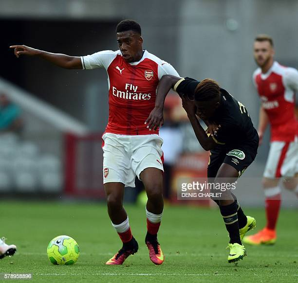 Arsenal's Nigerian forward Alex Iwobi vies with French Lens's forward Deme Ndiaye during the football match Lens versus Arsenal on July 22 2016 at...