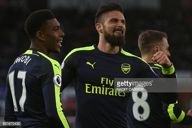 Arsenal's Nigerian striker Alex Iwobi celebrates his team's second goal with Arsenal's French striker Olivier Giroud after his shot was defelected...
