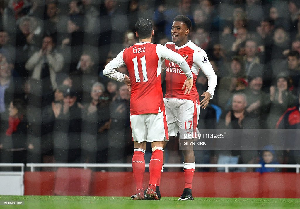 Arsenal's Nigerian striker Alex Iwobi (R) celebrates with Arsenal's German midfielder Mesut Ozil after scoring their third goal during the English Premier League football match between Arsenal and Stoke City at the Emirates Stadium in London on December 10, 2016. / AFP / Glyn KIRK / RESTRICTED TO EDITORIAL USE. No use with unauthorized audio, video, data, fixture lists, club/league logos or 'live' services. Online in-match use limited to 75 images, no video emulation. No use in betting, games or single club/league/player publications. /