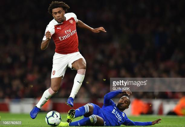 Arsenal's Nigerian striker Alex Iwobi evades a tackle from Leicester City's Portuguese defender Ricardo Pereira during the English Premier League...
