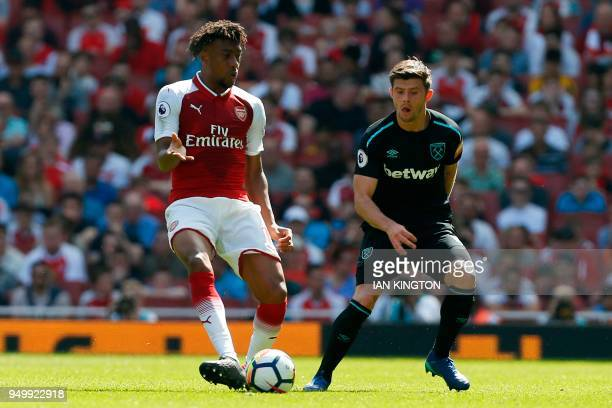 Arsenal's Nigerian striker Alex Iwobi plays the ball under pressure from West Ham United's English defender Aaron Cresswell during the English...