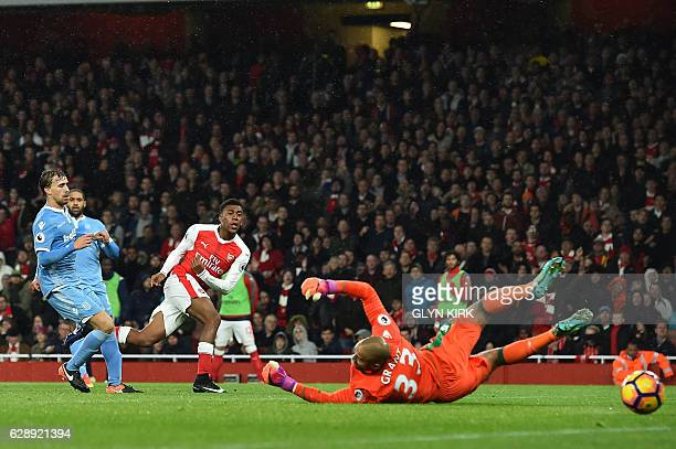 Arsenal's Nigerian striker Alex Iwobi shoots and scores past Stoke City's English goalkeeper Lee Grant during the English Premier League football...
