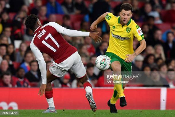 Arsenal's Nigerian striker Alex Iwobi vies with Norwich City's Dutch midfielder Yanic Wildschut during the first half of extra time in the English...