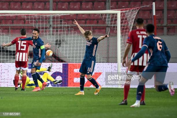 Arsenal's Norwegian forward Martin Odegaard celebrates after scoring his team's first goal during the UEFA Europa League round of 16 first-leg...