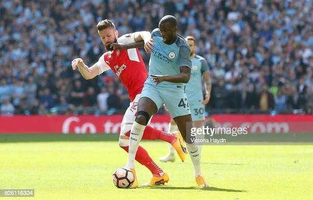 Arsenal's Olivier Giroud and Manchester City's Yaya Toure battle for the ball