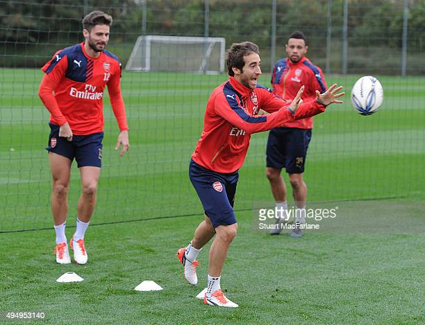 Arsenal's Olivier Giroud and Mathieu Flamini warm up with a rugby ball before a training session at London Colney on October 30 2015 in St Albans...