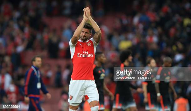 Arsenal's Olivier Giroud applauds the fans at the end of the match as Manchester United's players walk off dejected