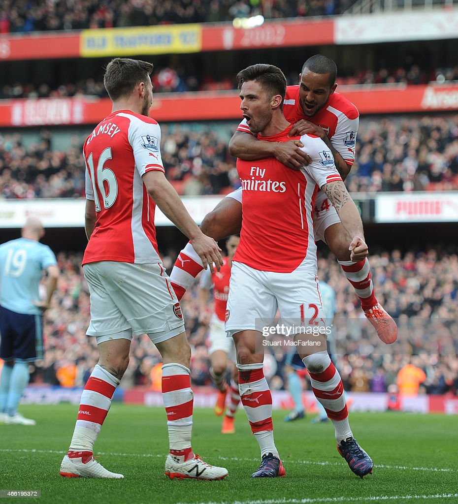 Arsenal's Olivier Giroud celebrates his goal with (L) Aaron Ramsey and (R) Theo Walcott during the Barclays Premier League match between Arsenal and West Ham United at Emirates Stadium on March 14, 2015 in London, England.