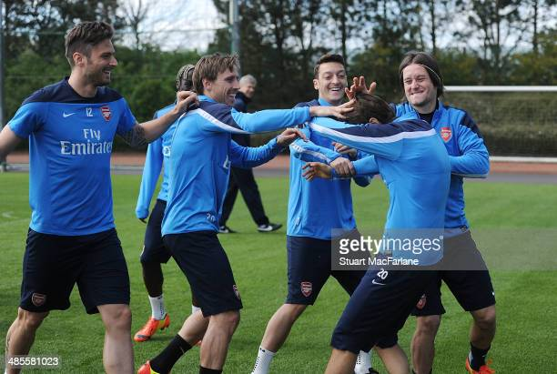 Arsenal's Olivier Giroud Nacho Monreal Mesut Ozil Mathieu Flamini and Tomas Rosicky mess around before a training session at London Colney on April...