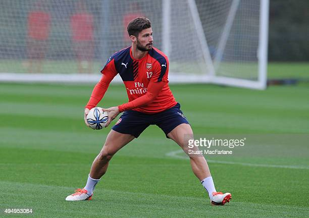 Arsenal's Olivier Giroud warms up with a rugby ball before a training session at London Colney on October 30 2015 in St Albans England