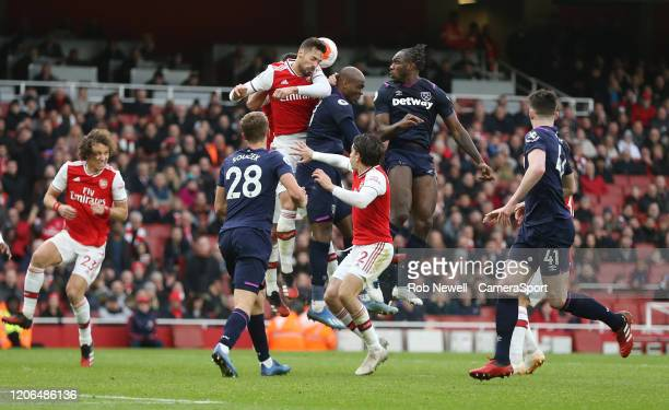 Arsenals Pablo Mari clears under the challenge of West Ham United's Angelo Ogbonna and Michail Antonio during the Premier League match between...