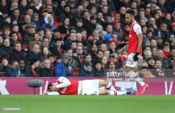Arsenal's PierreEmerick Aubameyang looks on at Sead Kolasinac who looks in pain after falling on his shoulder during the Premier League match between...