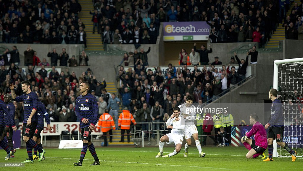 """Arsenal's Polish goalkeeper Wojciech Szczesny (2nd R) and midfielder Jack Wilshere (R) look on as Swansea City's English striker Danny Graham (4th R) celebrates scoring his team's second goal to equalise late in the game with teammate Ki Sung-Yueng (3rd R) during the FA Cup third round football match at the Liberty Stadium in Swansea, Wales, on January 6, 2013. The game ended with a 2-2 draw. USE. No use with unauthorized audio, video, data, fixture lists, club/league logos or """"live"""" services. Online in-match use limited to 45 images, no video emulation. No use in betting, games or single club/league/player publications."""