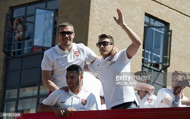 Arsenal's Polishborn German striker Lukas Podolski Arsenal's German midfielder Serge Gnabry and Arsenal's German midfielder Mesut Ozil wave to fans...