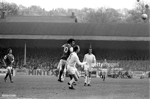 Arsenal's Ray Kennedy heads the ball out to the wing watched by Leeds United's Jack Charlton and Paul Madeley