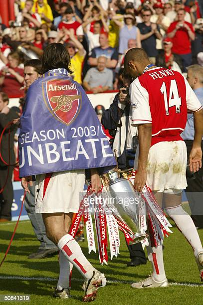 Arsenal's Robert Pires and Thierry Henry carry the Premiership trophy after winning the Premiership title and defeating Leicsester City 15 May 2004...