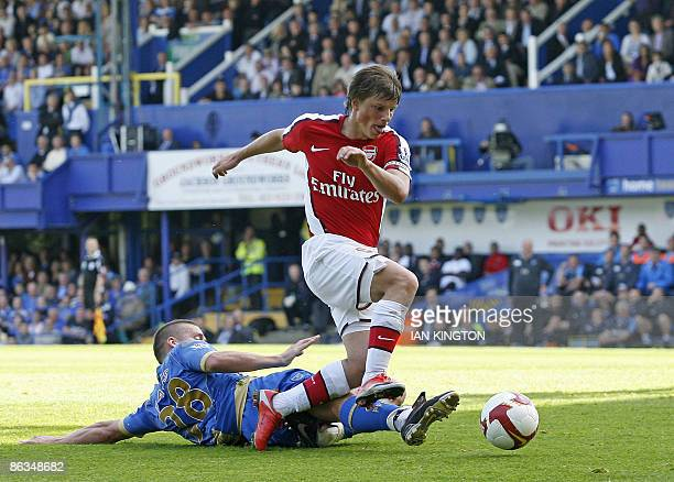 Arsenal's Russian player Andrey Arshavin is challenged by Portsmouth's English midfielder Sean Davis giving away a penalty during the Premier League...